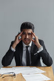 Deprimierter Geschäftsmann, der am Tisch mit den Dokumenten, Kamera betrachtend sitzt Stockfotos