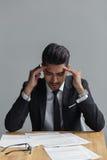 Deprimierter Geschäftsmann, der am Tisch mit Dokumenten sitzt Lizenzfreies Stockbild
