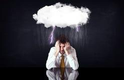 Deprimierter Geschäftsmann, der unter einer Wolke sitzt Stockfotografie
