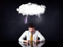 Deprimierter Geschäftsmann, der unter einer Wolke sitzt Lizenzfreies Stockbild