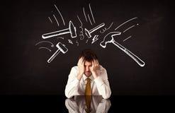 Deprimierter Geschäftsmann, der unter Hammerzeichen sitzt Stockbilder