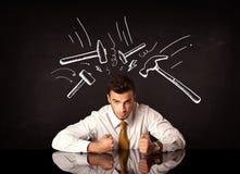 Deprimierter Geschäftsmann, der unter Hammerzeichen sitzt Lizenzfreie Stockfotos
