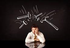 Deprimierter Geschäftsmann, der unter Hammerzeichen sitzt Stockbild
