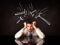 Deprimierter Geschäftsmann, der unter Hammerzeichen sitzt Lizenzfreies Stockfoto