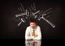 Deprimierter Geschäftsmann, der unter Hammerzeichen sitzt Lizenzfreies Stockbild