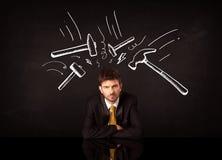 Deprimierter Geschäftsmann, der unter Hammerzeichen sitzt Lizenzfreie Stockfotografie