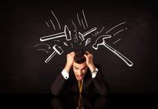 Deprimierter Geschäftsmann, der unter Hammerzeichen sitzt Stockfoto