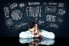Deprimierter Geschäftsmann, der unter Problemgedankenkästen sitzt Stockfotos