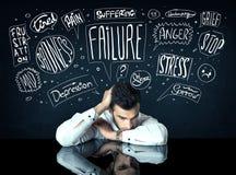 Deprimierter Geschäftsmann, der unter Problemgedankenkästen sitzt Lizenzfreies Stockbild