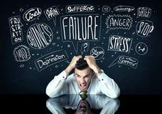 Deprimierter Geschäftsmann, der unter Problemgedankenkästen sitzt Lizenzfreies Stockfoto