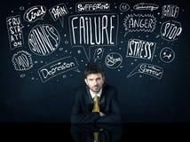 Deprimierter Geschäftsmann, der unter Problemgedankenkästen sitzt Stockfoto