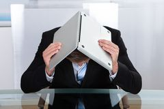 Deprimierter Geschäftsmann, der unter seinem Laptop sich versteckt stockbild