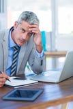 Deprimierter Geschäftsmann, der versucht zu arbeiten Lizenzfreies Stockbild