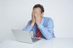 Deprimierter Geschäftsmann-With Laptop At-Schreibtisch Stockfoto