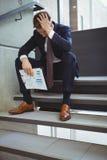 Deprimierter Geschäftsmann mit dem Klemmbrett, das auf Treppe sitzt Lizenzfreies Stockfoto
