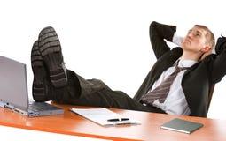 Deprimierter Geschäftsmann mit den Fahrwerkbeinen auf Tabelle Lizenzfreie Stockfotos