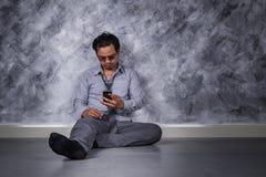 Deprimierter Geschäftsmann mit Handy und Sitzen auf dem Boden Lizenzfreie Stockbilder