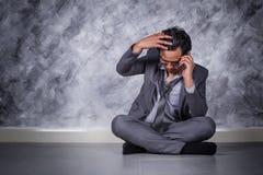 Deprimierter Geschäftsmann mit Handy und Sitzen auf dem Boden Lizenzfreie Stockfotografie