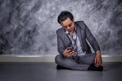 Deprimierter Geschäftsmann mit Handy und Sitzen auf dem Boden Stockbilder
