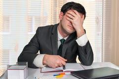 Deprimierter Geschäftsmann mit Kopfschmerzen im Büro Lizenzfreie Stockfotografie