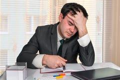 Deprimierter Geschäftsmann mit Kopfschmerzen im Büro Lizenzfreie Stockfotos