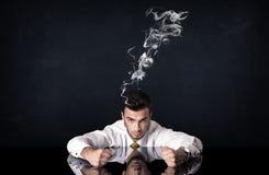 Deprimierter Geschäftsmann mit rauchendem Kopf Stockbild