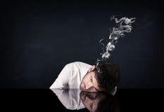 Deprimierter Geschäftsmann mit rauchendem Kopf Stockfoto