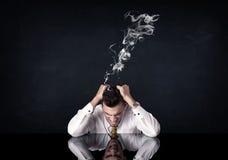 Deprimierter Geschäftsmann mit rauchendem Kopf Stockfotos