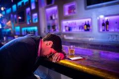 Deprimierter getrunkener Mann, der auf dem Tisch mit seinem Kopf schläft Stockbild
