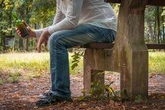 Deprimierter getrunkener Mann mit der Bierflasche, die auf Bank sitzt Lizenzfreie Stockbilder