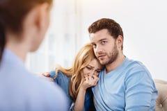Deprimierter gutaussehender Mann, der seine Frau umarmt Lizenzfreie Stockfotografie