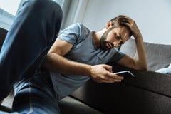 Deprimierter gutaussehender Mann, der seinen Smartphone verwendet Stockfoto