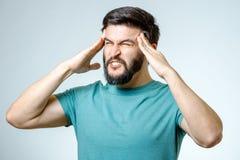 Deprimierter hübscher bärtiger Mann, der Kopfschmerzen habend sich berührt Lizenzfreie Stockfotos