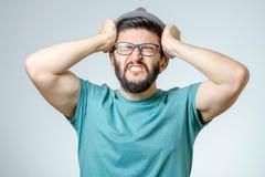 Deprimierter hübscher bärtiger Mann, der Kopfschmerzen habend sich berührt Lizenzfreie Stockfotografie