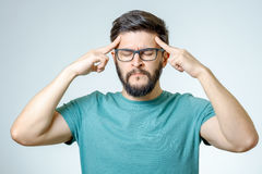 Deprimierter hübscher bärtiger Mann, der Kopfschmerzen habend sich berührt Stockfotografie
