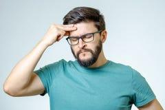 Deprimierter hübscher bärtiger Mann, der Kopfschmerzen habend sich berührt Stockbild