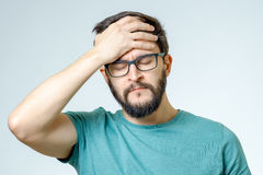 Deprimierter hübscher bärtiger Mann, der Kopfschmerzen habend sich berührt Stockfotos
