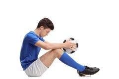 Deprimierter Jugendfußballspieler, der auf dem Boden sitzt Lizenzfreie Stockfotos