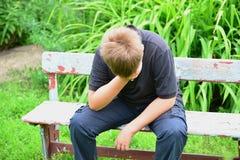 Deprimierter Jugendlicher, der auf der Bank sitzt Lizenzfreie Stockfotos