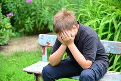 Deprimierter Jugendlicher, der auf der Bank sitzt Stockbilder