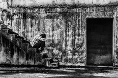 Deprimierter Jugendlicher, der auf Treppe im gruseligen verlassenen Gebäude sitzt Lizenzfreie Stockfotografie