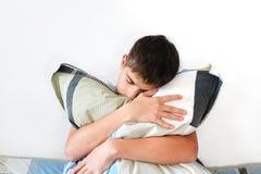 Deprimierter Jugendlicher mit Kissen Stockfotografie