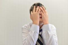 deprimierter Jugendlichjunge bedeckte sein Gesicht mit seinen Händen Stockbilder
