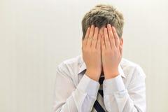 deprimierter Jugendlichjunge bedeckte sein Gesicht mit seinen Händen Stockfoto