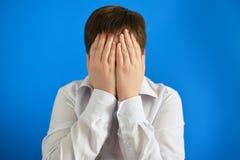 deprimierter Jugendlichjunge bedeckte sein Gesicht mit seinen Händen Lizenzfreie Stockfotos