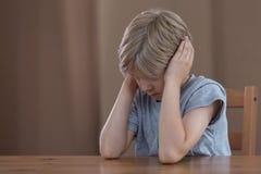 Deprimierter Junge, der Ohren verstopft Lizenzfreie Stockfotos