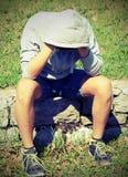 Deprimierter Junge mit und Turnschuhe mit Weinleseeffekt Stockfoto