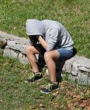 Deprimierter Junge, während er an Selbstmord wegen des Neckens denkt Stockbild