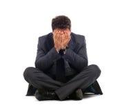 Deprimierter junger Geschäftsmann, der aus den Grund sitzt Lizenzfreie Stockbilder