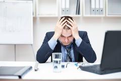 Deprimierter junger Geschäftsmann, der seinen Kopf anhält Stockbild